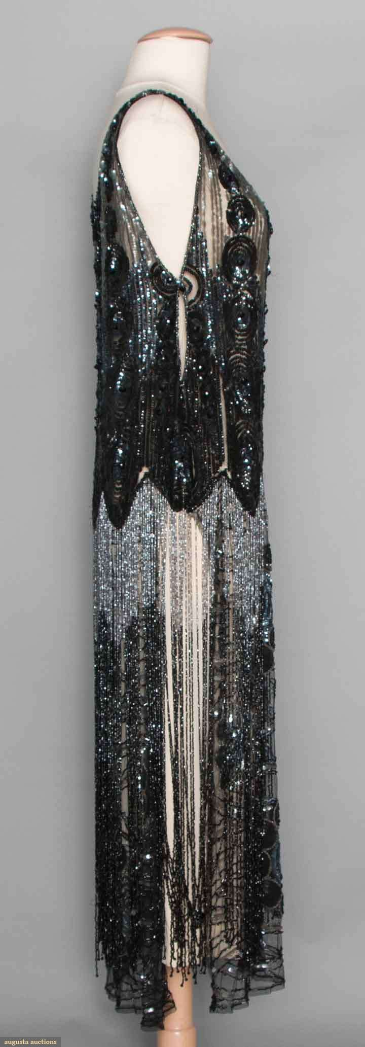 "SEQUINED & BEADED TABARD, c. 1925. Black net, shoulder to hip area covered w/ black & gunmetal sequins in dense circular patterns, stylized branch & blossom pattern below hip to hem is partially concealed by 20+"" long beaded fringe. Sideway"