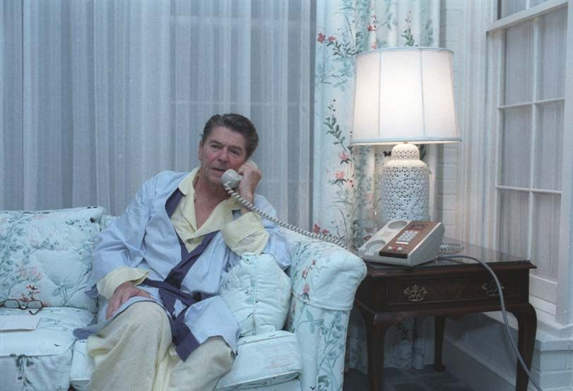 President Ronald Reagan making an early morning telephone call to staff regarding the situation in Grenada.... at Eisenhower cabin, Augusta National Golf course in Georgia. 10/22/83.