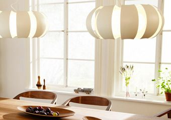 Two white STOCKHOLM pendant lamps hanging over a dining ...