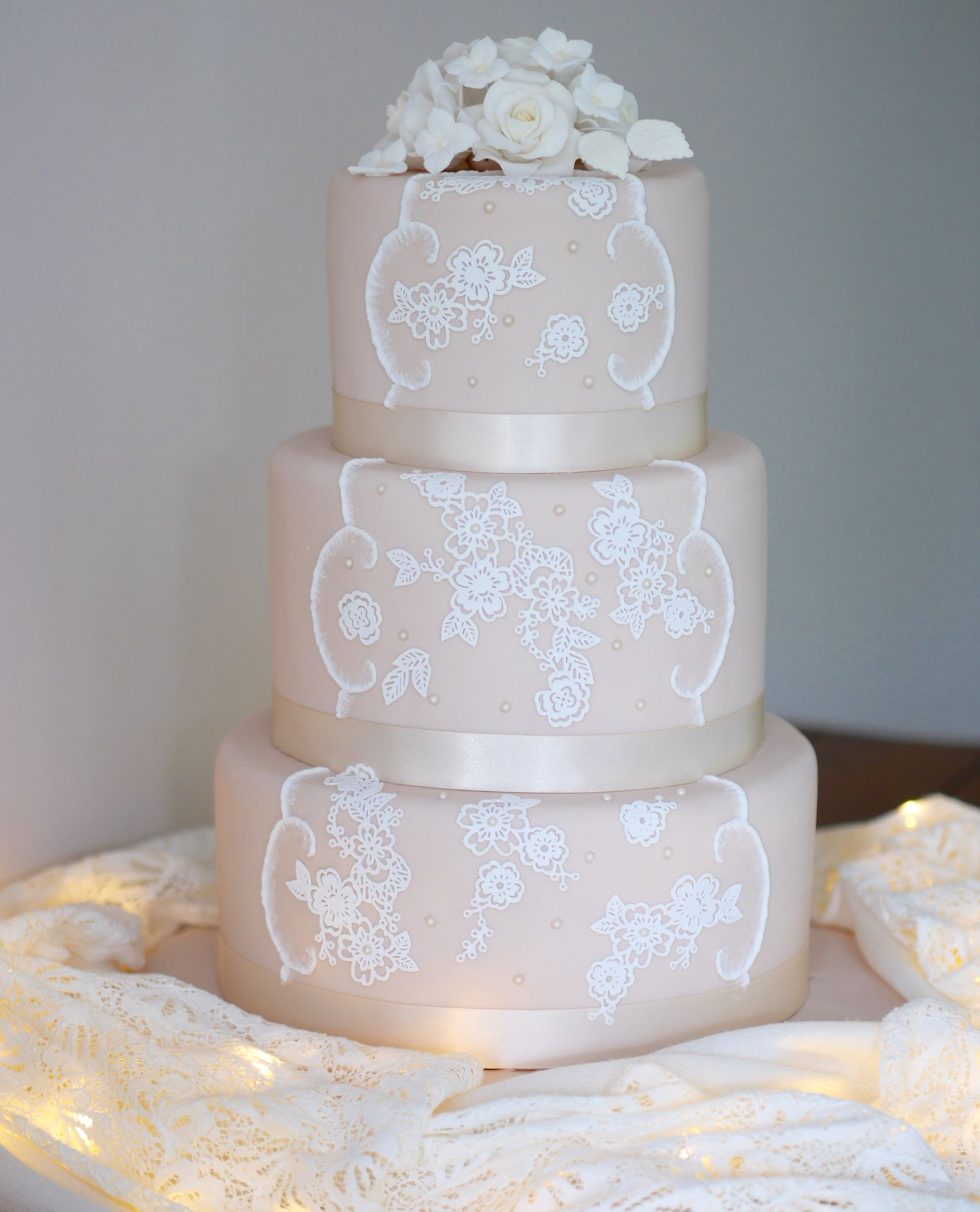 Lace cake with white gumpaste flowers the lace was created using