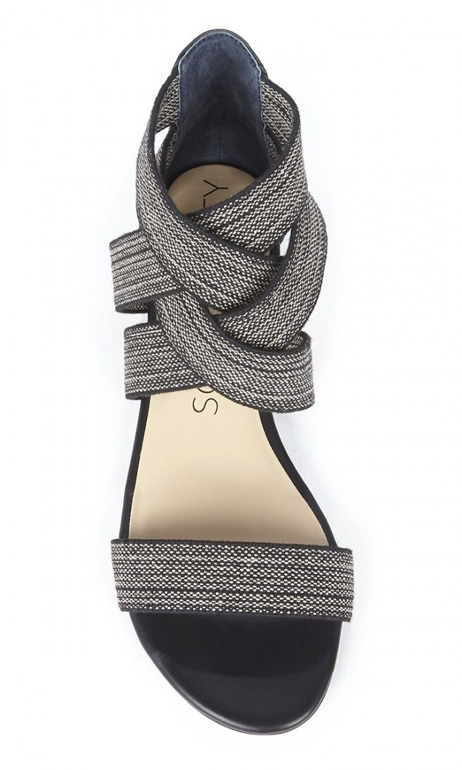 Black & white elastic flat sandals with crisscrossing straps at the ankles and an open toe strap