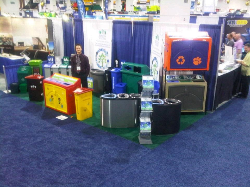 John displaying the newly set up booth at Waste Expo showcasing a full line of recycling containers and compost bins. School recycling containers take center stage!