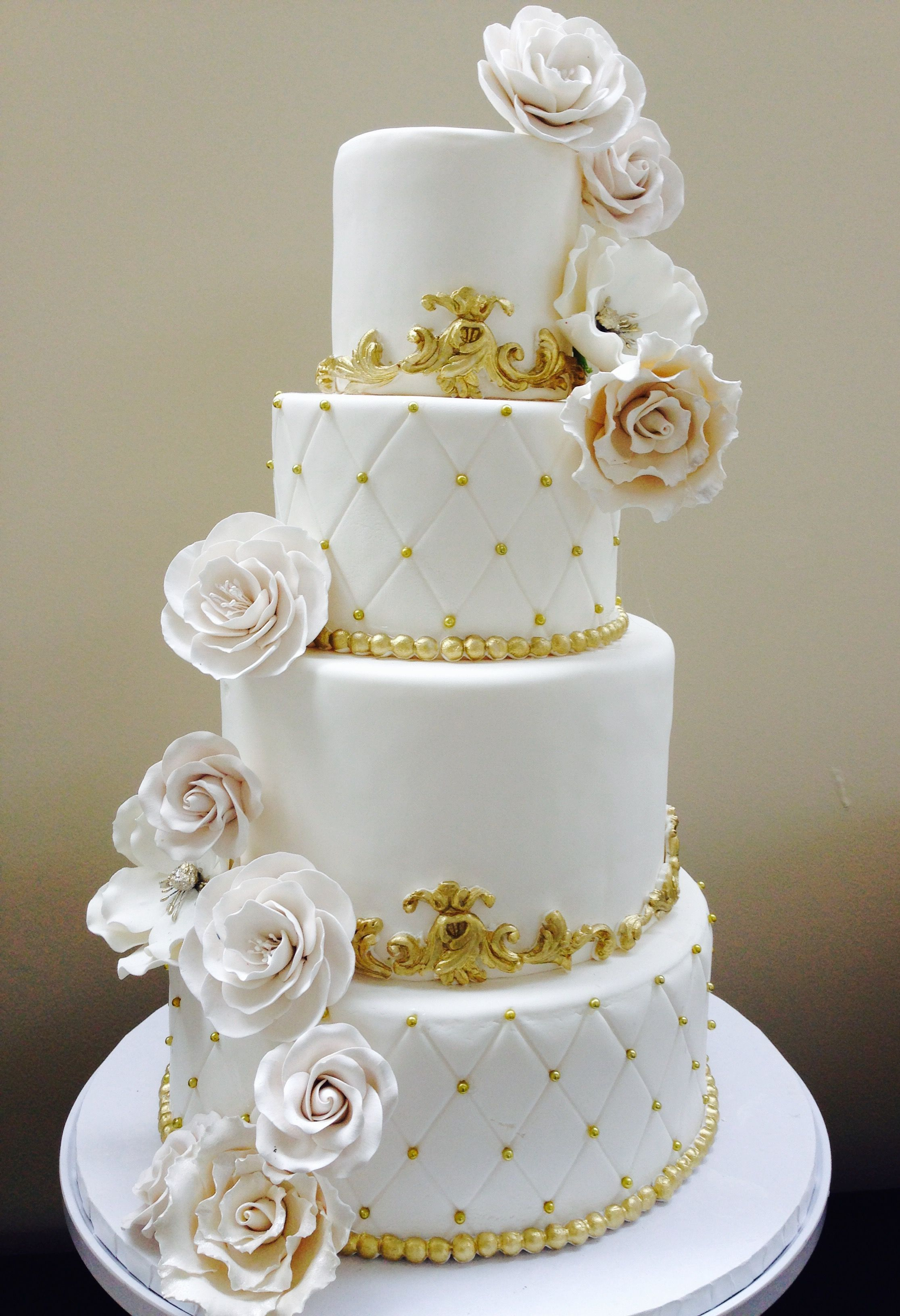 All white wedding cake with gold accents.