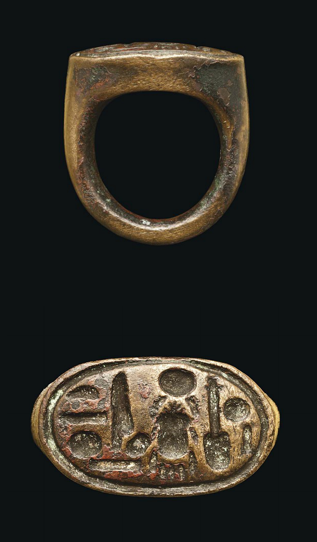 AN EGYPTIAN BRONZE STIRRUP RING   NEW KINGDOM, DYNASTY XVIII, AMARNA PERIOD, REIGN OF AKHENATEN, 1353-1335 B.C.  With the hieroglyphic inscription reading, 'Nefer kheperu re, sa Iten', 'Perfect are the manifestations of Ra, Son of Aten', the throne name of Akhenaten  1 in. (2.5 cm.) wide