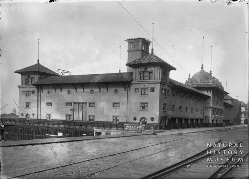 View of the Redondo Beach Bathing Pavilion. Its domed roof is decorated with seahorses. A sign for Lemon's Studio appears on the lower level. Keywords: bathhouses, seahorses, domes, Lemon's studio, streetcar tracks, rails, bathing houses.