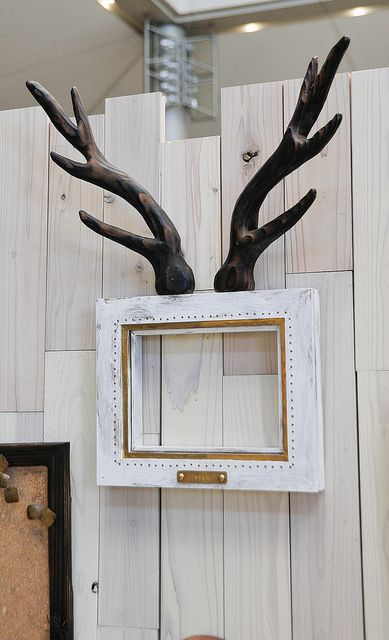 White, worn, wooden picture frame with antlers. ホワイト、木製の鹿の角がついている額縁。Tokyo, Japan