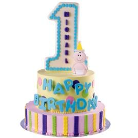 Celebrate this number one birthday in the biggest way! Create a candy plaque number 1; decorate the 2 tiered cake with easy-to-work-with fondant letters and trim.