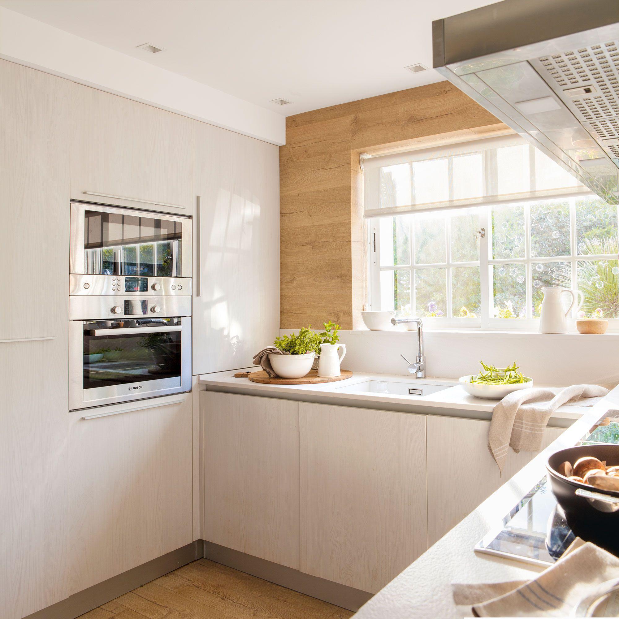 Cocina con pared revestida de madera y una pared de armarios con los ...