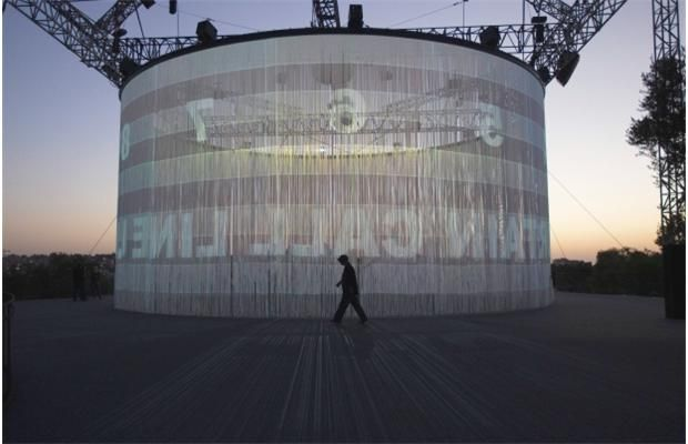 """A man walks past Israeli designer Ron Arad's video installation in the Art Garden at the Israel Museum in Jerusalem August 14, 2012. Arad's piece, """"720 degrees"""", is a circular screen made up of 5,600 silicon ropes that hang down from a circular frame 8 meters above ground. Video pieces by different artists from around the world are projected onto the screen."""