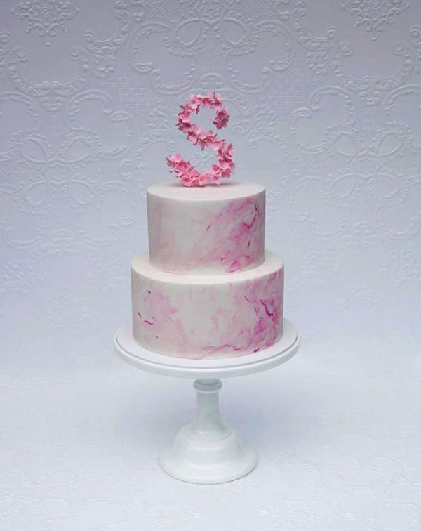 pink marbled cake topped with letter s
