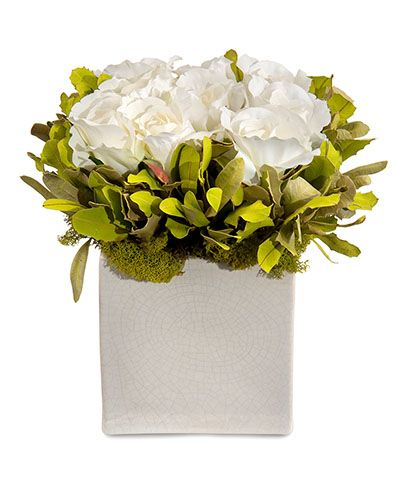 Sweet Nothing Pave Botanical - The lushness of pavé floral styling takes on a more relaxed, garden quality in this beautiful permanent arrangement, the Sweet Nothing Pavé Botanical. Rooted in a simple vase of white crackle ceramic, the old-world white roses bloom densely within a bed of wildly lovely chartreuse foliage. A rim of moss softens the look with a dreamy, woodsy effect.