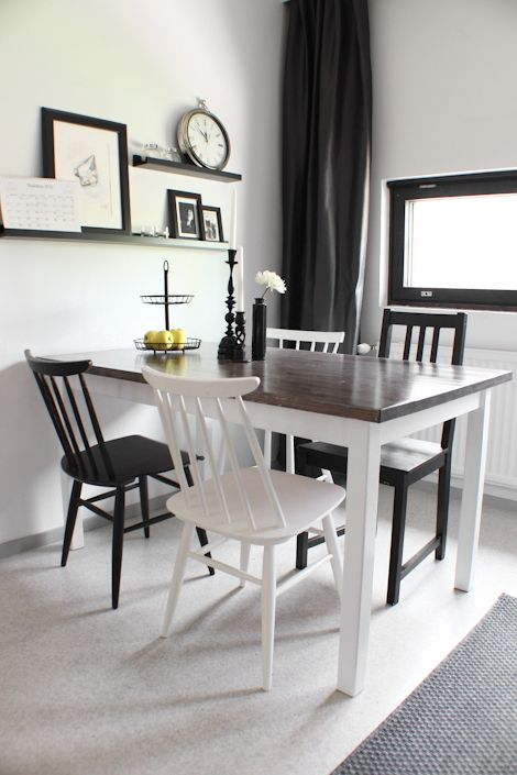 Dining table with wooden top and white legs and black and white chairs