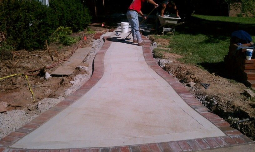 Concrete walkway with a brick boarder by t h foundations