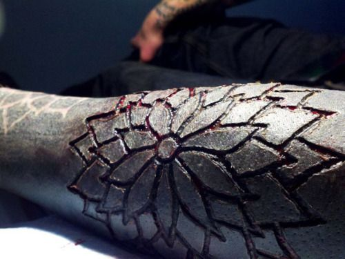 Scarification over black out tattoo on forearm for Skin works tattoo