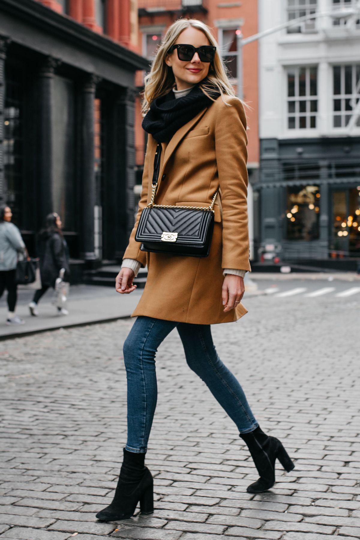 Blonde Woman Wearing Camel Coat Black Scarf Denim Skinny Jeans Black  Booties Chanel Black Boy Bag