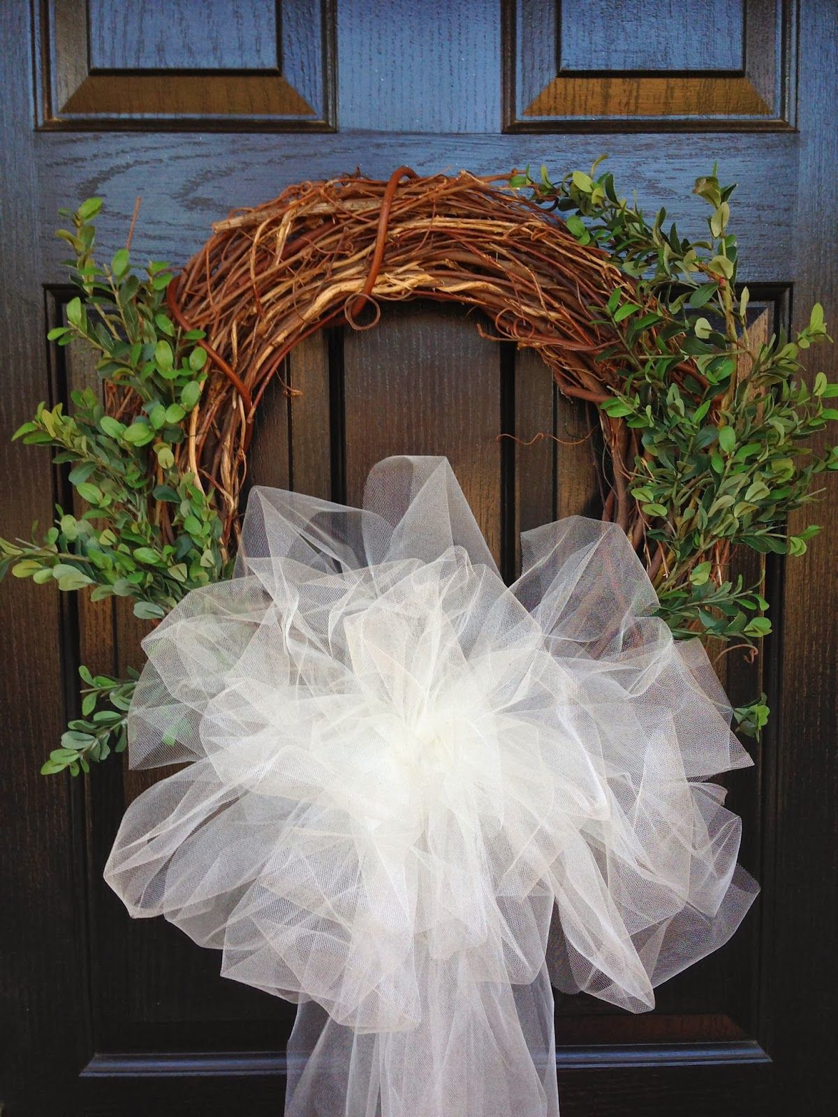 Simple grape vine wreath with boxwood cuttings and tulle bow. Nice for Wedding Engagement, wedding or anniversary events.