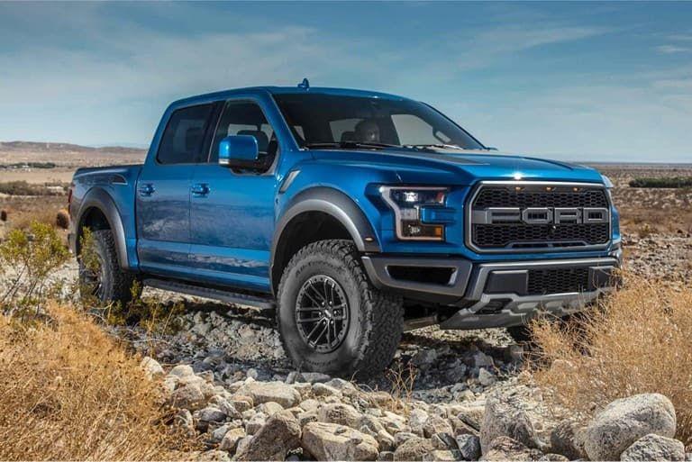 Velocity Blue Raptor Parked On Rocks Ford Pickup Trucks Raptor