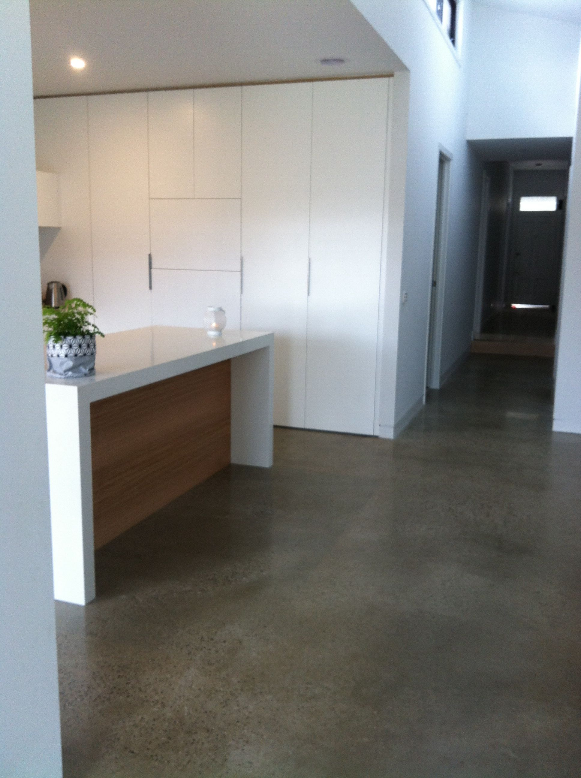 Kitchen with polished concrete floor, white stone benchtop and ...