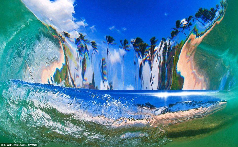 En la foto: un disparo desde detrás de una ola rompiente mirando hacia la orilla.  Aquí, el fotógrafo Clark Little, está bajo el agua y la curva de la onda distorsiona la escena de la playa alargando las palmeras.