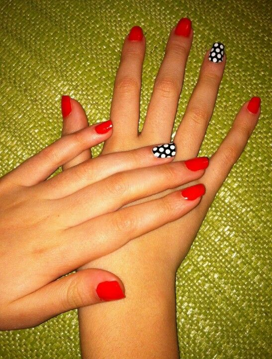 Red nails with a polka dot accent