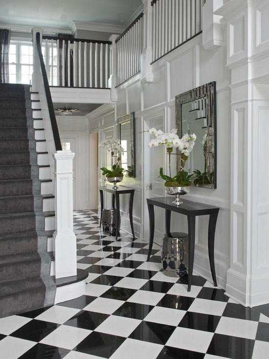 Chic Foyer With Silver Stools Tucked Under Black Console