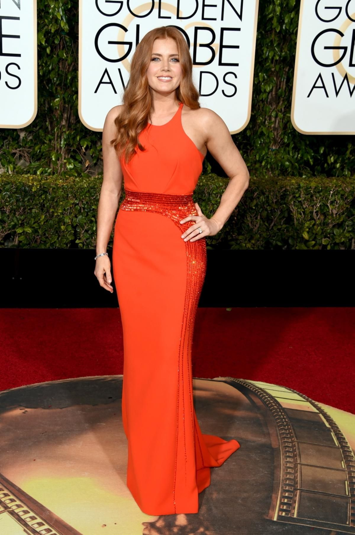 Actress Amy Adams struck a pose in a figure-hugging red Atelier Versace gown, embellished with beads that accentuate her waist at the 2016 Golden Globes on Jan. 10, 2016.