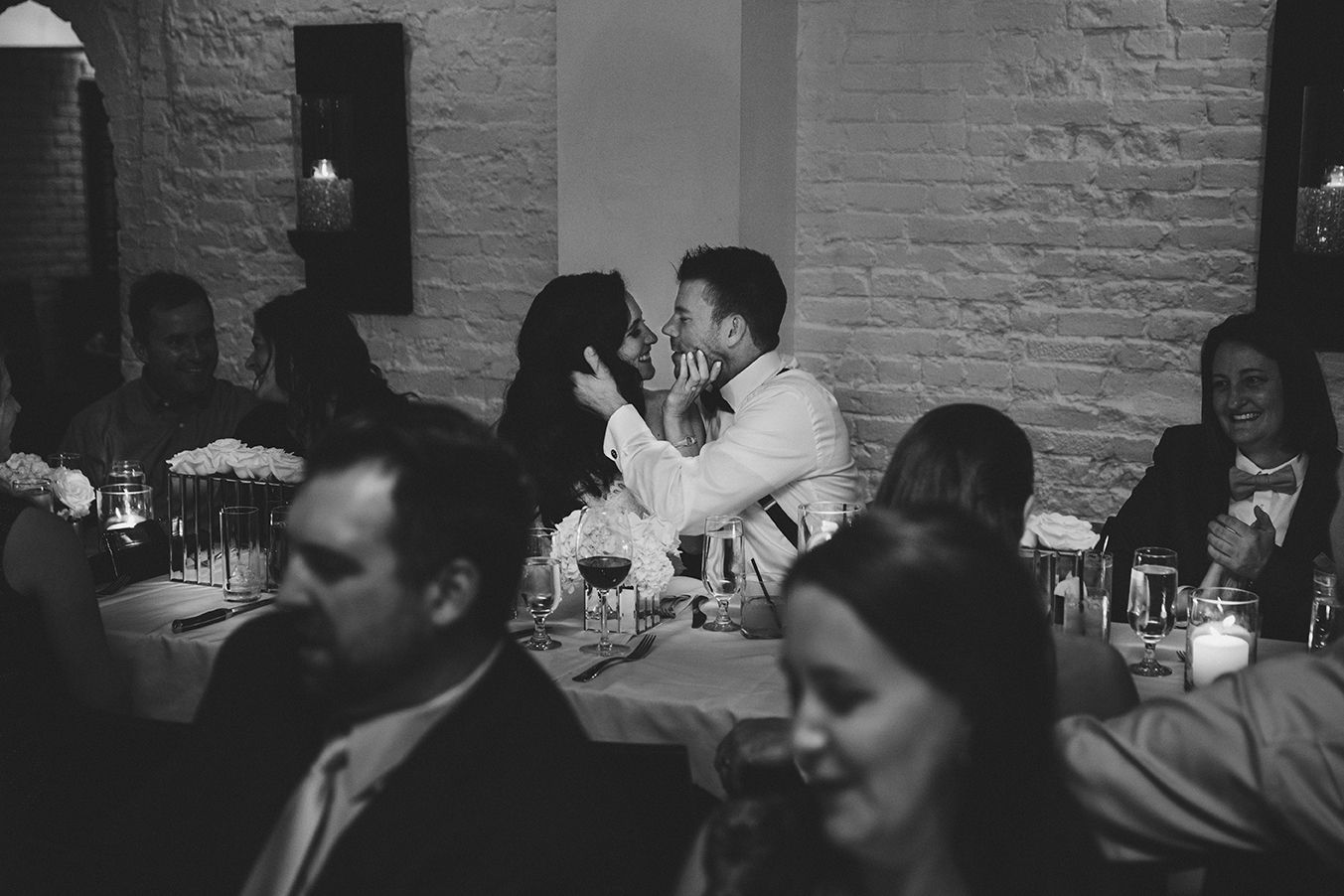 A documentary photograph of a bride and groom kissing during their