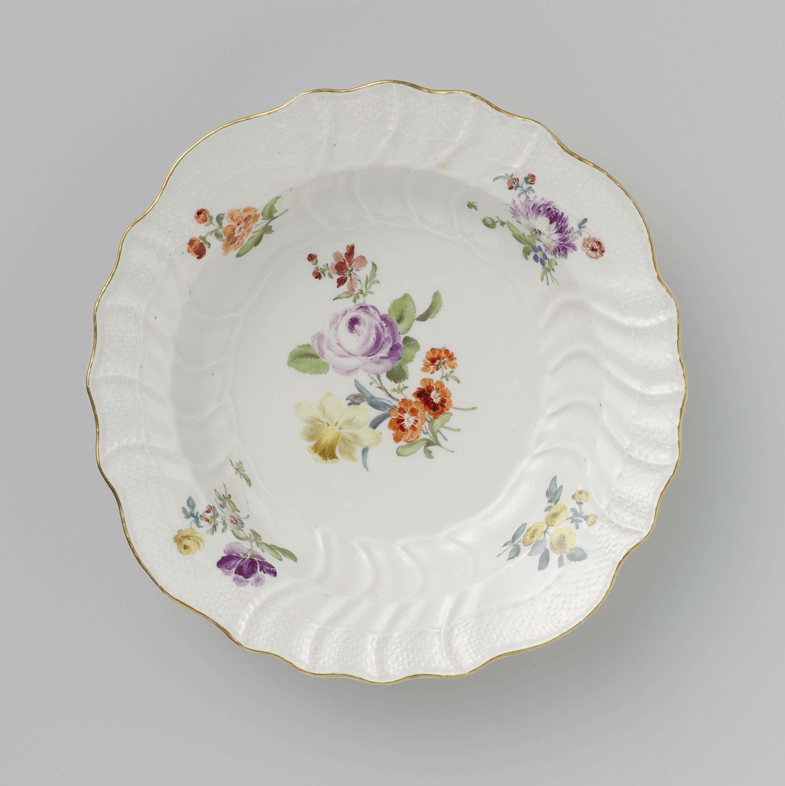 Meissener Porzellan Manufaktur | Bord, veelkleurig beschilderd met Deutsche Blumen, insekten en vruchten, Meissener Porzellan Manufaktur, c. 1750 - c. 1760 | Rond soepbord van beschilderd porselein. Het bord is beschilderd met Deutsche Blumen, insekten en vruchten. De rand is in reliëf versierd met het Neuozier-patroon. Het bord is gemerkt en hoort bij een servies (BK-17474-1 t/m BK-17474-253).