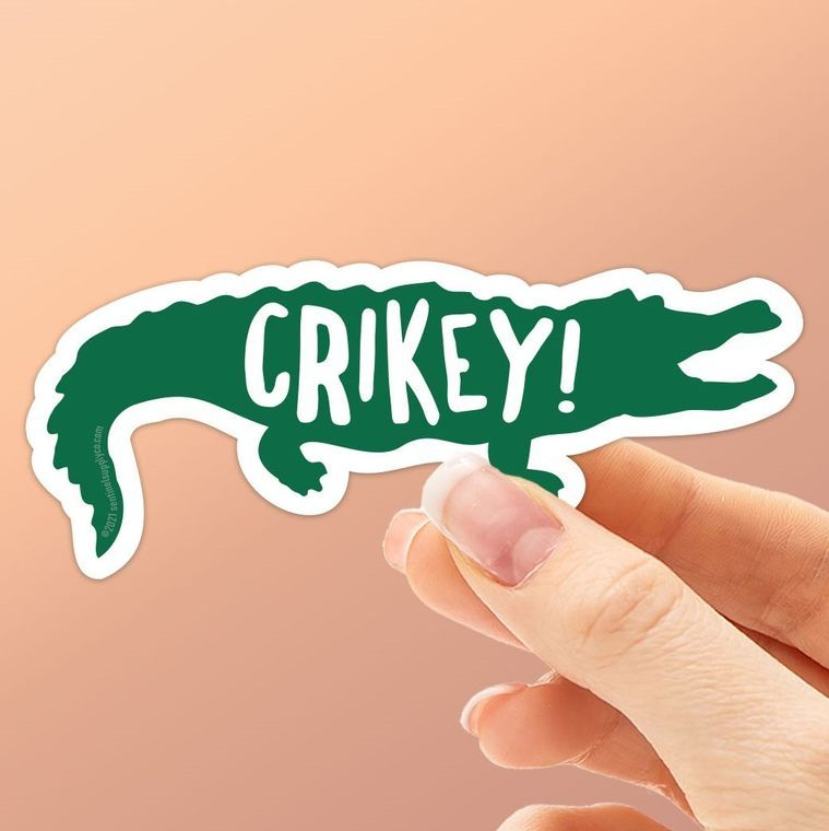 Crikey! Whether you're an Aussie, an Australian tourist, or a fan of the old Crocodile Hunter TV series with Steve Irwin, you'll recognize this quintessential Australian slang expression of surprise. This cute crocodile sticker is perfect for all those who love reptiles, the Australia Zoo, Crocodile Dundee quotes, or all 3. Stick this waterproof vinyl decal on your Hydroflask, thermos, cooler, or laptop. It's a smaller size, perfect for filling in the empty spaces between stickers!  Dimensions: