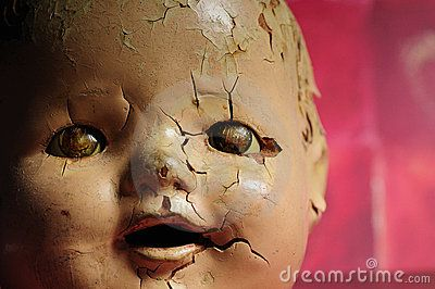 cracked doll head | Creepy old doll head shot against a red textured background.