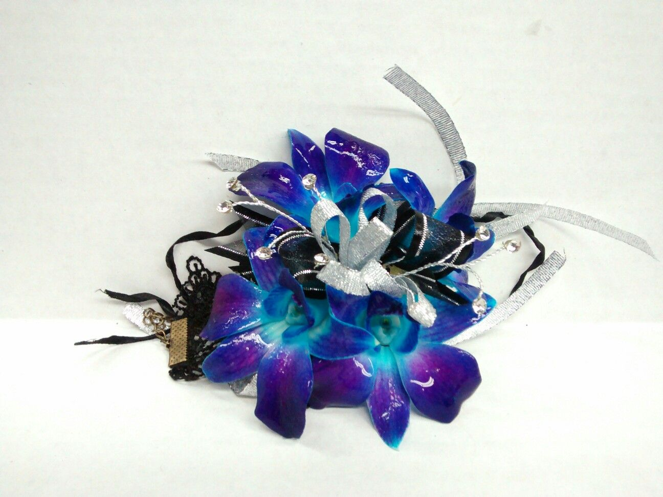 Blue dendrobium orchid corsage with lace wristlet and silver accents