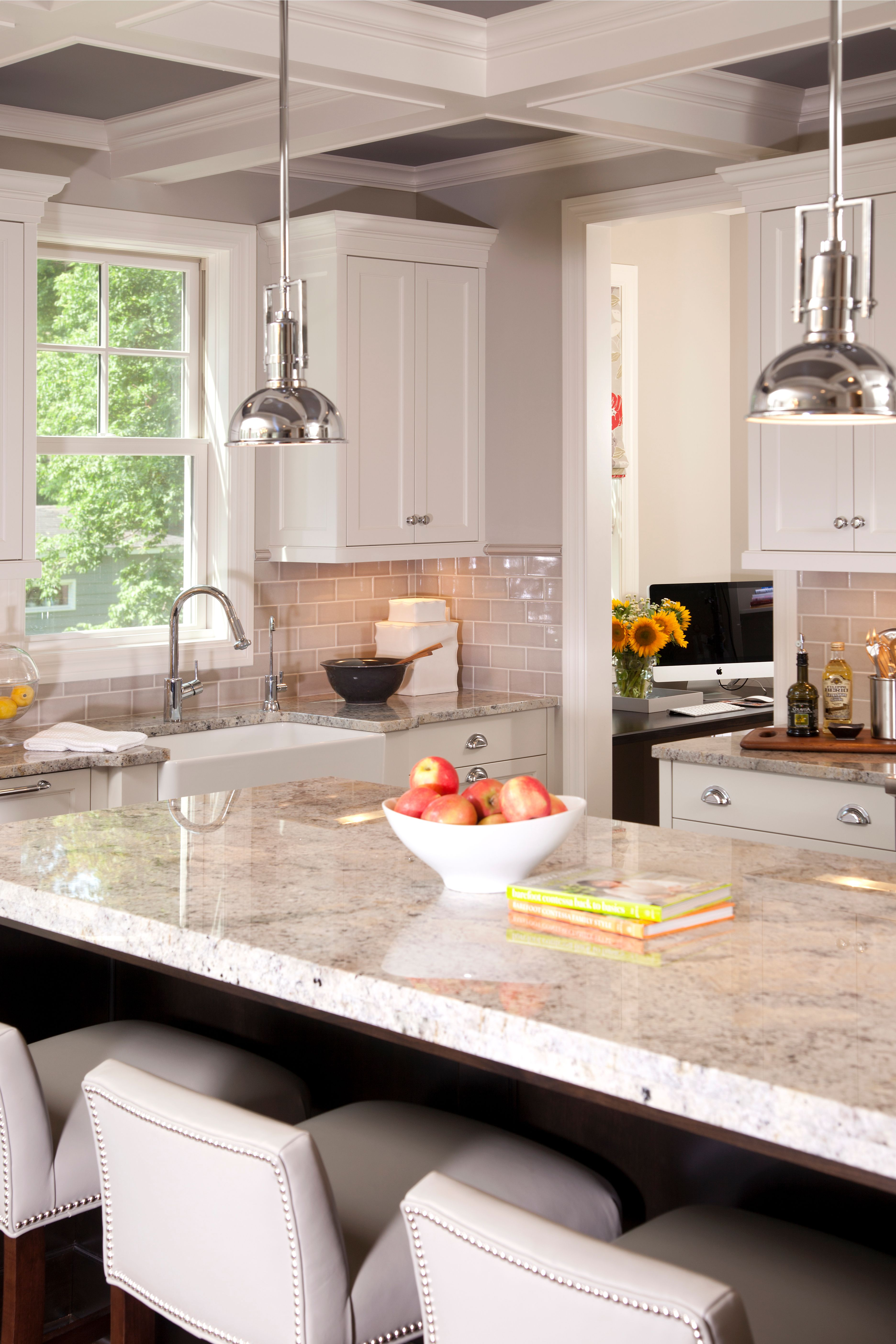 White marble island and two pendant lights overhanging with bright