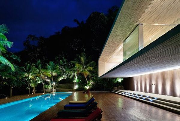 Paraty House by Marcio Kogan Architects features two reinforced concrete boxes, stacked on top of each other. The house, which projects off the mountainside and onto the beach, is located on an island in the city of Paraty (between São Paulo and Rio de Janeiro).    The home includes an extensive open doorway system that seamlessly blends the indoors and outdoors into one gorgeous living space.