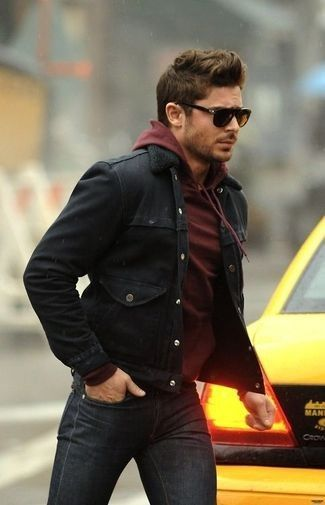 Zac Efron Is Wearing A Black Denim Jacket A Dark Red Pullover With A Hood Dark Gray Jeans Mens Outfits Burgundy Hoodie Black Denim Jacket