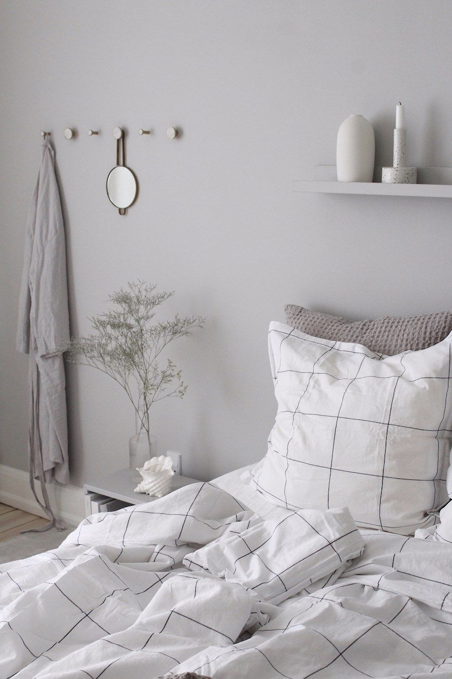 Light blue marble wallpaper behind all white bedding and