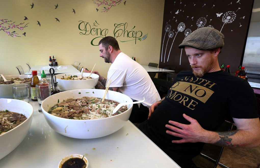 Pastry chef Matt Tinder, front, feels the Challenge at Dong Thap Noodles. Chef Miles James, rear, posts a photo of his bowl to Facebook on his phone. (Ken Lambert/The Seattle Times)