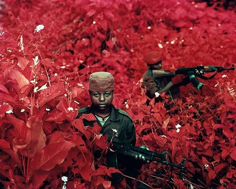 Wow!    Extreme tourism'. That's what Richard Mosse describes his field of photo-journalism as. His work really stands out as unique art amongst the plethora of press photographs of war-torn countries. Using infra-red film, the landscapes surrounding his military subjects jump out of the frame as a clash of vibrant magentas and violets, celebrating the natural environment which often goes forgotten in times and places of conflict.