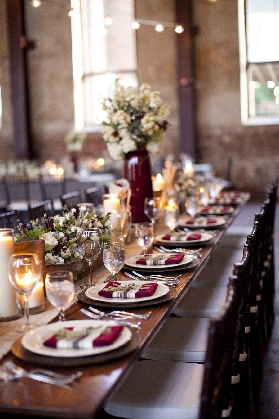 maroon themed wedding reception decorations with maroon vases and