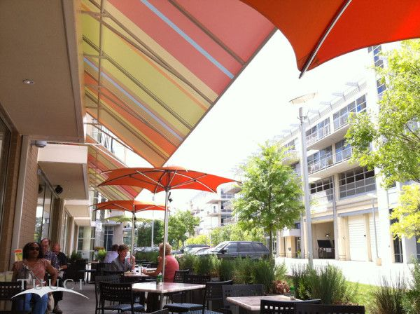 These orange TUUCI Crescent parasols look great at Zoes Kitchen in ...