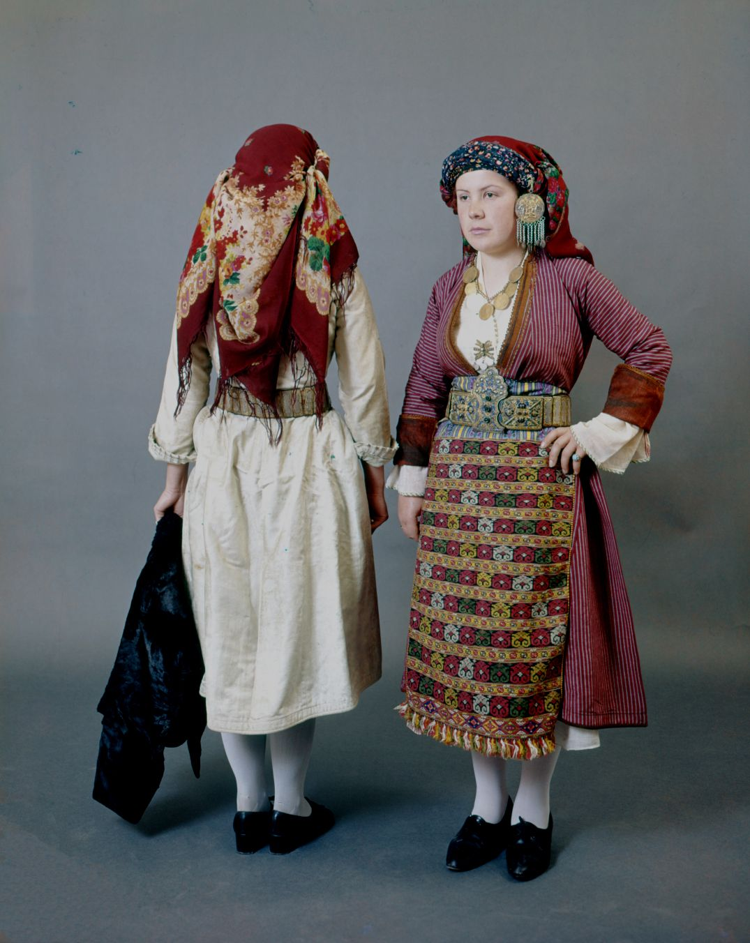 "foulard a frange, asymetrie, bijou  Two women's costumes from the village of Soufli in Thrace back and front. The woman's dress coat is known by the name of ""kaftani"" made of striped silk red material and is worn over a unique curly silk chemise. The headdress is composed of two scarves and a typical temple ornament ""paouni"" depicting the nativity.  Size 	  Date 	Early 20th c."
