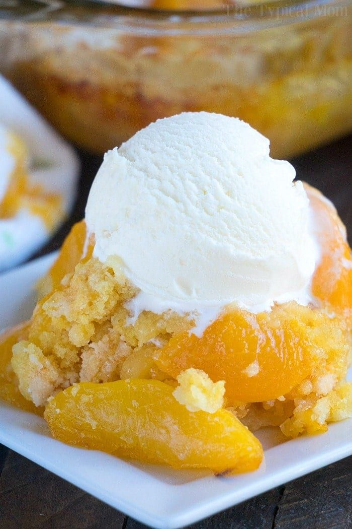 This dump peach cobbler requires just 4 ingredients & topped with vanilla ice cream it is the warm dessert you've been dreaming about. Dump cake perfection! #peach #dumpcake #piefilling #dessert #cobbler #fruit