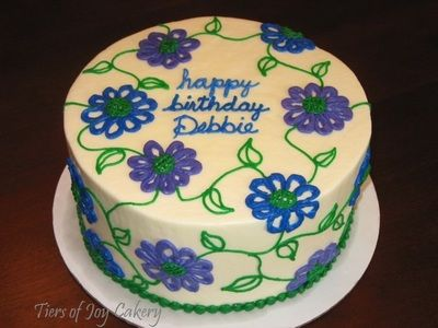 Birthday cake with purple and blue flowers and green vines