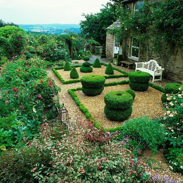 A formal gravel garden with mature box topiary edged in English