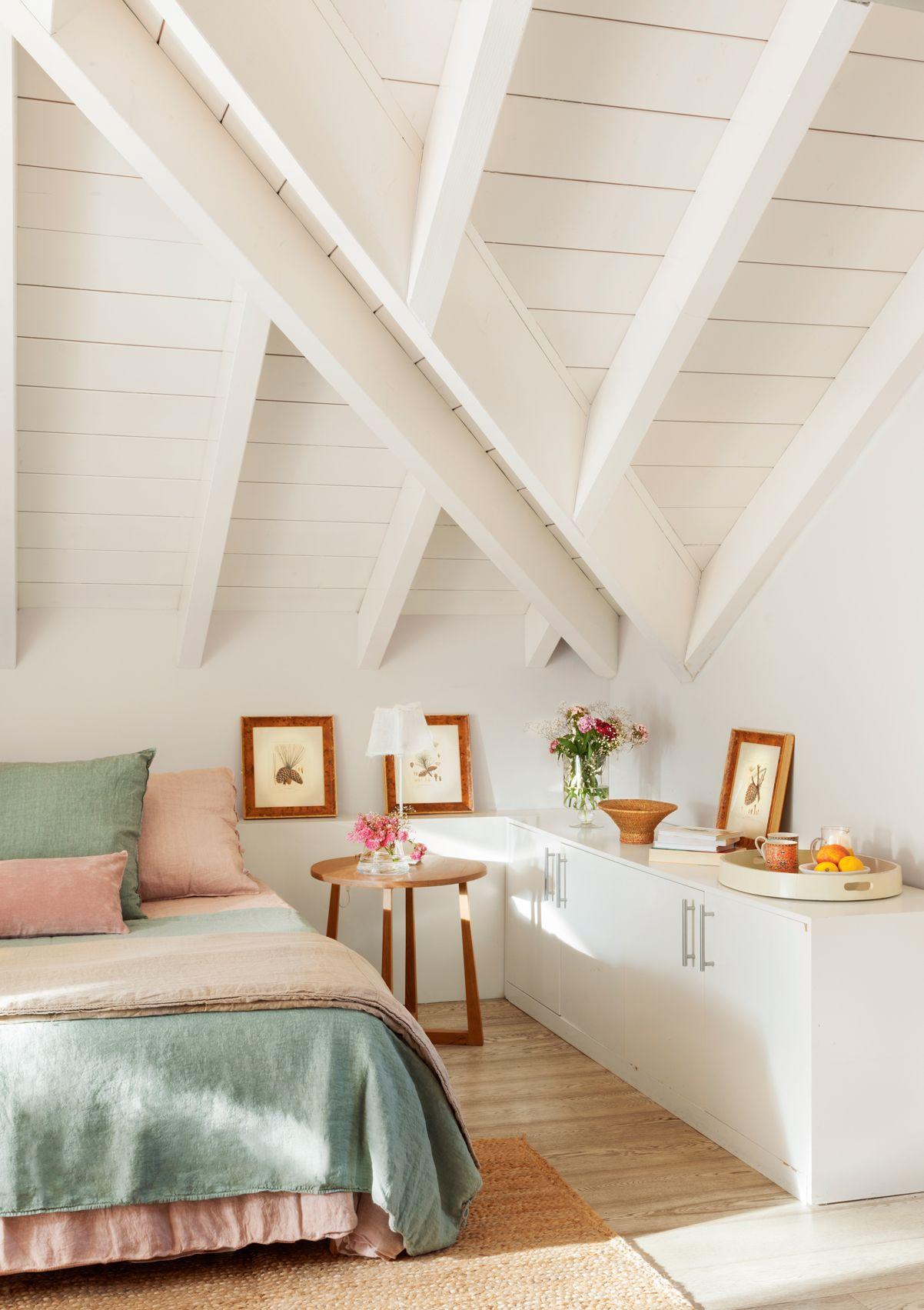 Dormitorio en buhardilla con envigado blanco mueble bajo cuadros