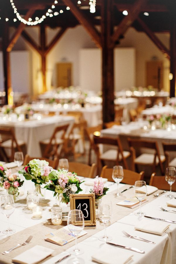 Rustic venue with burlap runners, gold frames, bottles of flowers, and votives. Perfect.