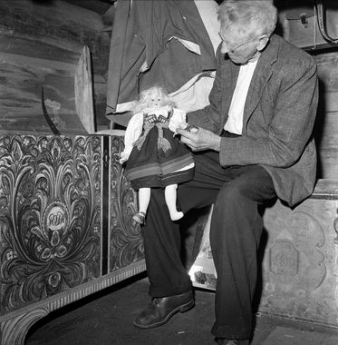 DigitaltMuseum - Sølvsmed Knut Sigurdsson Helle fra Valle i Aust-Agder, antakelig. Sitter med en bunadsdokke ved en rosemalt kiste.