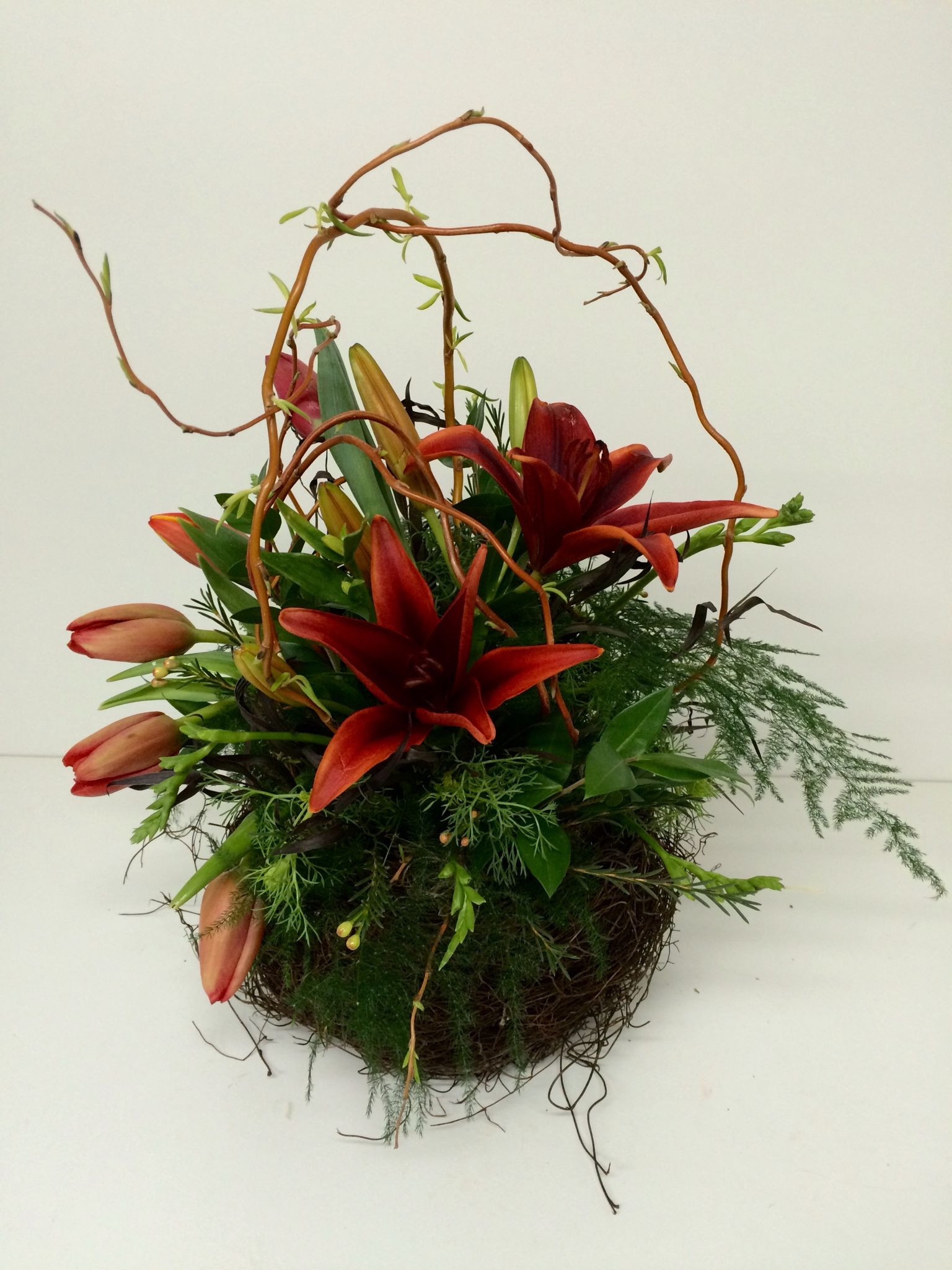 A Nest Style Basket Filled With Red Tulips And Lilies And A Touch Of Budding Curly Willow Red Tulips Flower Arrangements Tulips