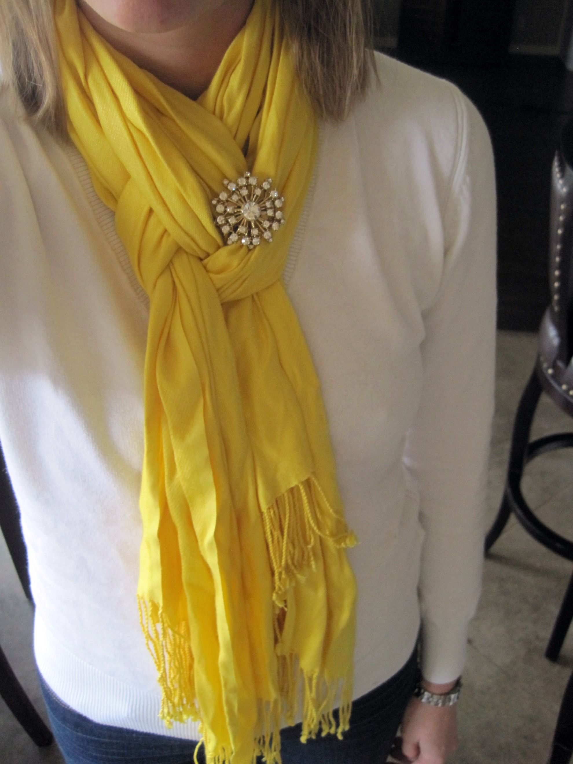 Fold scarf in half. Loop around neck. Pull only one strand of the scarf through the loop. Twist loop, then pull other strand through. Leave as is, or adorn with a brooch.