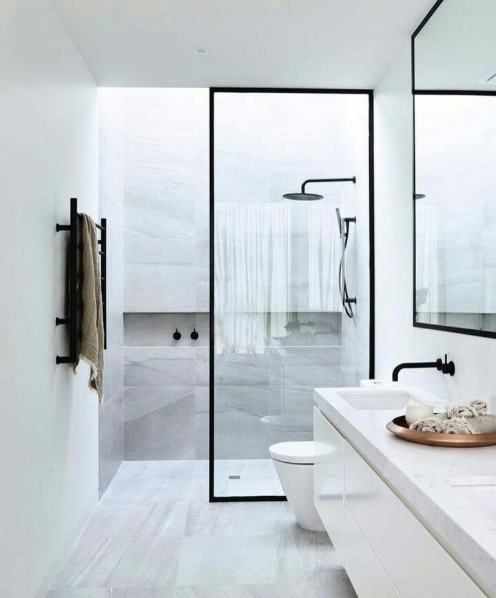 Bathroom with black framed glass walk-in shower. This contemporary bathroom idea is so sleek and beautiful. Shampoo niche goes the length of this beautiful shower with a rain head.