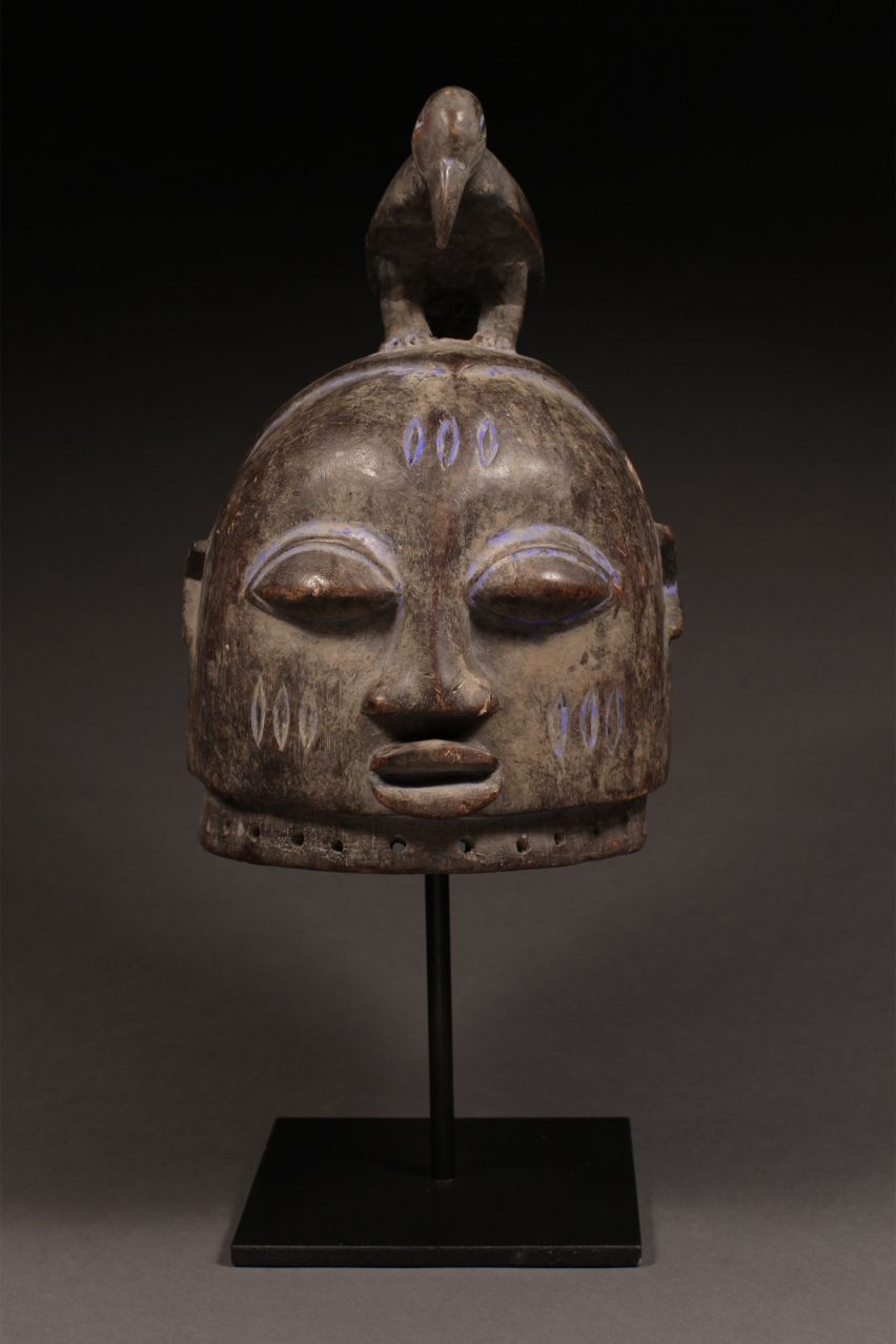 """Gelede Mask Yoruba Tribe, Nigeria Wood, kaolin pigment  H: 14"""" (20"""" on display stand)  The Gelede masquerade is a rich spectacle of drama, dance, poetry, and drumming, that plays an important role in Yoruba culture. The masquerade is held between March and May when the rains arrive and a new agricultural cycle begins, and is performed by male members of a ritual cult who have been trained in the arts of masking from the age of four or five. The Gelede masquerade tells of the hi"""